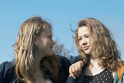 Teenage girls looking at each other and smiling, Freiburg im Breisgau, Baden-Wuerttemberg, Germany