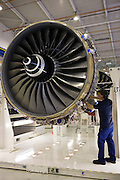 Enginer works on a Rolls Royce jet engine in the production factory, Derbyshire, United Kingdom