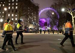 © Licensed to London News Pictures. 31/12/2018. London, UK. Event security personnel walk along an empty Whitehall in sight of the London Eye ferris wheel before the crowds arrive to celebrate New Year's Eve in central London.  Over 100,000 people are attending London's ticketed fireworks display on the banks of the River Thames for New Year's Eve tonight. Photo credit: Peter Macdiarmid/LNP