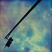 A stoplight on the end of a pole extends diagonally across the frame with interesting clouds above