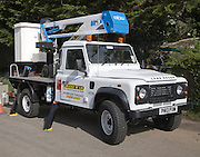 Land Rover vehicle with cherry picker crane mounted on its back rented from Truck R Us, UK