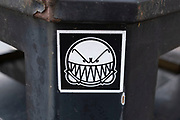 Street art paste up smiley yet angry face with teeth by Tempo 33 stuck onto a bin on 10th October 2020 in Birmingham, United Kingdom. Tempo33 is a Birmingham-based street artist who is known for paste up black and white faces.