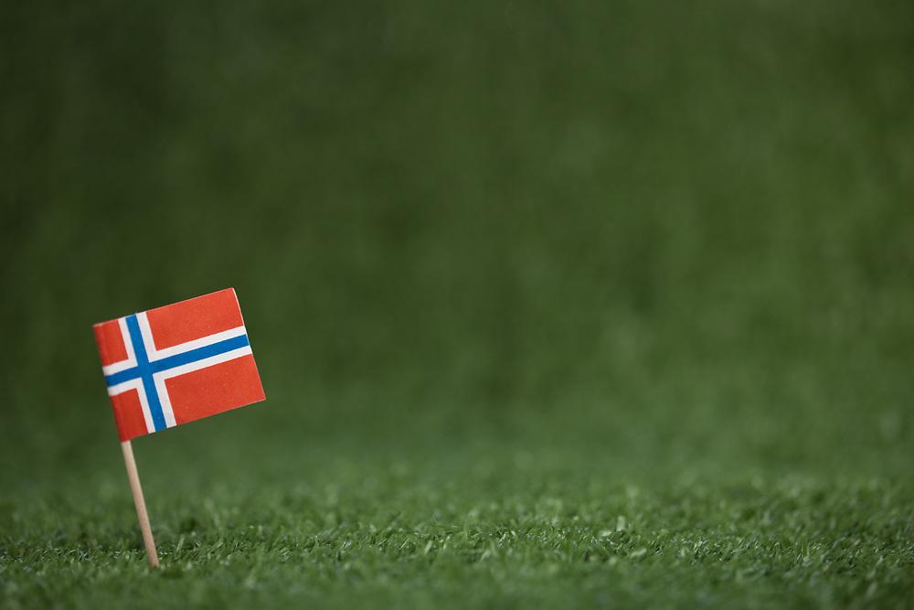 Ett norsk flagg med trepinne på grønt kunstress. Foto tatt med macro-objektiv, stor dybdeuskarphet. God plass til tekst, spesielt egnet som bakgrunnsbilde.