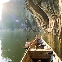 Boy watches as Will Hair rappels into the Nam Ou River, Ban Pak Ou, Luang Phrabang, Laos