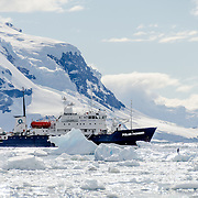 A ship (Polar Pioneer) amongst the brash ice and icebergs of Neko Harbour, Antarctica.