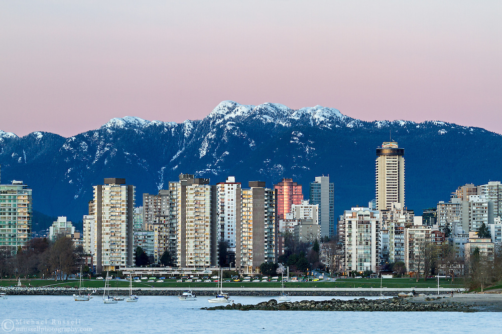 Condo and Apartment towers in the West End of Vancouver British Columbia. Fresh winter snow on Mount Seymour is in the background and the waters of English Bay in the foreground.  Photographed from Kits Beach Park in Kitsilano.