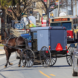 Intercourse, PA / USA - April 6, 2015: An Amish buggy moves through the heavy traffic in the Lancaster County village.