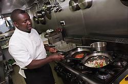 Chef frying food in Caribbean restaurant kitchen,