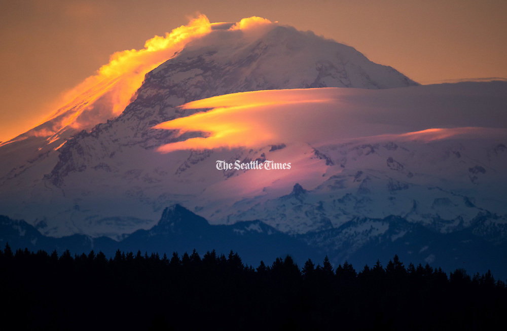 Mount Rainier looms in this telephoto view from Lake Forest Park during Thursday morning's sunrise. The mountain appears to be steaming as clouds form and change as the sun hits the mountain. (Mike Siegel / The Seattle Times, 2021)