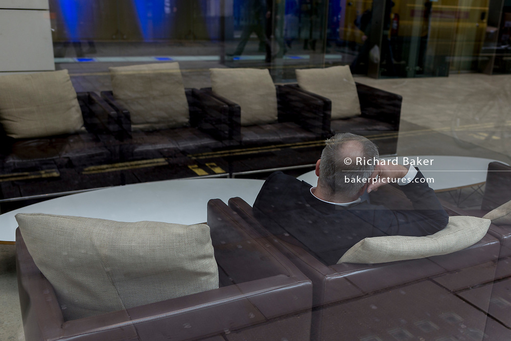 Rear view of a businessman waiting on seats in an office reception foyer, on 8th March 2017, London borough of Westminster, England.