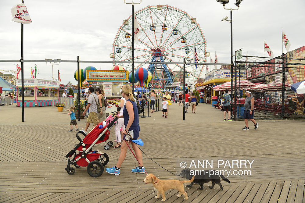 Brooklyn, New York, USA. 10th August 2013. A fwoman pushing a baby stroller walks two dogs on a leash on the famous Coney Island boardwalk along Luna Park, during the 3rd Annual Coney Island History Day celebration.