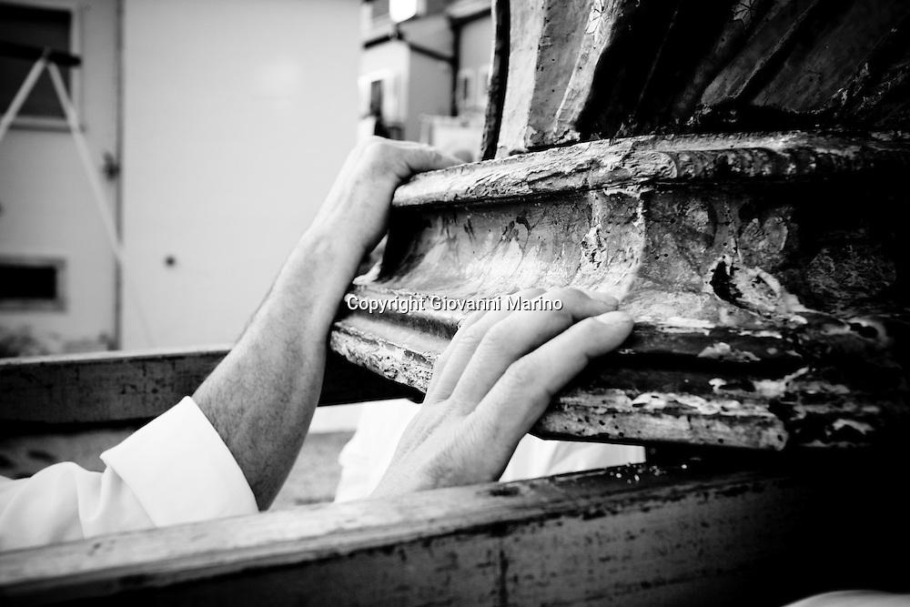"""Pescopagano (PZ) 02/07/2008 - Volo dell'Angelo. A Pescopagano, (PZ), 1' Angelo è un bambino di otto- nove anni; per tradizione lo stesso bambino deve """"volare"""" per due anni consecutivi. Rappresenta genericamente un Angelo """"buono""""; indossa un corto vestito di veli bianchi, ali profilate di ferro ricoperte di tulle, elmo e sandali dorati. Il volo dell'Angelo viene effettuato una prima volta in occasione della festa di san Francesco di Paola, il 30 giugno. L'Angelo è cinto da un nastro celeste con la scritta CHARITAS in oro. II volo è ripetuto, dal medesimo bambino-angelo, il 2 luglio per la festa della Madonna delle Grazie, e allora il nastro è bianco con la scritta AVE MARIA. In entrambe le feste il volo è effettuato nella piazza del Municipio dove è allestito un palco coperto di teli celesti; da qui parte un cavo, fissato a un palo di ferro antistante, su cui vien fatto scarrucolare l'Angelo per mezzo di un argano elettrico. Arrivato sulla perpendicolare delle due statue, esibite entrambe nelle due feste, il bambino-Angelo pronuncia frasi di saluto e di richiesta di protezione, quindi offre fiori e incenso."""