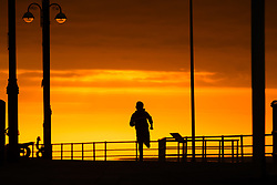 © Licensed to London News Pictures.<br /> Aberystwyth UK, 26/03/2019<br />  A beautiful sunset , at the end of another day of warm spring sunshine, silhouettes a boy running along the promenade  in Aberystwyth, on the Cardigan Bay coast of west Wales. High pressure continues to dominate the weather for much of the UK, with settled conditions and clear blue skies<br /> photo Keith Morris/LNP