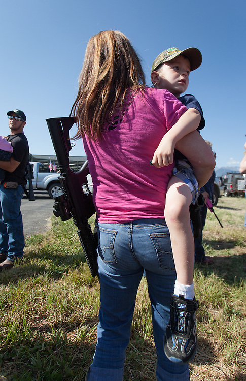 """A mother holds her son and her weapon, as several hundred gun-rights supporters gather in a parking lot before marching with their weapons down Main Street in Westcliffe, Colo., as part of an Independence Day Parade. Many brought their children. A few brought animals. A flyer promoting the armed march was circulated throughout southern Colorado, calling on """"patriots"""" to bring their guns - especially the """"evil black ones"""" - and display them in the annual parade."""