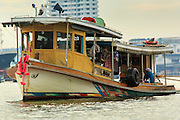 "17 NOVEMBER 2012 - BANGKOK, THAILAND: A tug boat pulls barges up the Chao Phrya River in Bangkok. Bangkok used to be known as the ""Venice of the East"" because of the number of waterways the criss crossed the city. Now most of the waterways have been filled in but boats and ships still play an important role in daily life in Bangkok. Thousands of people commute to work daily on the Chao Phraya Express Boats and fast boats that ply Khlong Saen Saeb or use boats to get around on the canals on the Thonburi side of the river. Boats are used to haul commodities through the city to deep water ports for export.    PHOTO BY JACK KURTZ"