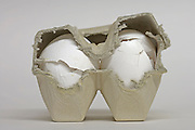 two extra large broken eggs in a to small egg carton