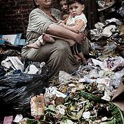 """Una mujer frente a su casa abraza a sus nietos en un descanso durante el trabajo de separación de los desechos orgánicos del resto de la basura recolectada. En medio del barrio de Manshiet Nasr a las afueras de El Cairo esta situado el asentamiento de Mokattam conocido como la """"Ciudad de la Basura"""" , está habitado por los Zabbaleen ,una comunidad de unos 45.000 cristianos coptos que viven desde hace varias décadas de reciclar los desperdicios que genera la capital egipcia: plástico, aluminio, papel y desechos órganicos que transforman en compost . La mayoría forman parte de la Asociación para la Protección del Ambiente (APE) una ONG que actúa en el área, cuyos objetivos son proteger el medio ambiente y aumentar el sustento de las recuperadores de basura de El Cairo. Según la ONU, el trabajo que se realiza en Mokattam como uno de los diez mejores ejemplos del mundo en el mejoramiento medioambiental. El Cairo , Egipto, Junio 2011. ( Foto : Jordi Camí )<br /> « less"""