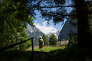 A walker emerges into sunlight in the Triglavski Narodni Park in the Slovenian Julian Alps, on 22nd June 2018, in Trenta, Triglav National Park, Slovenia. Nearby mountains are Kreiski 2050m, Pihavec 2419m, Dolina Zadnjica and Triglav 2864m.