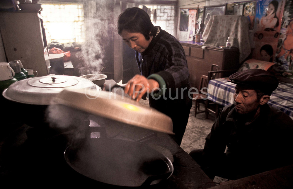 Du Cai Mei prepares a meal with the help of her husband, Chang Lin, Chang Qu village, Shaanxi, China.