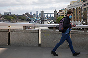 Man passing wearing face mask on London Bridge with Tower Bridge in the background, which is normally bustling with pedestrians, very few people are out, and it is eerily quiet and silent as lockdown continues and people observe the stay at home message in the capital on 11th May 2020 in London, England, United Kingdom. Coronavirus or Covid-19 is a new respiratory illness that has not previously been seen in humans. While much or Europe has been placed into lockdown, the UK government has now announced a slight relaxation of the stringent rules as part of their long term strategy, and in particular social distancing.