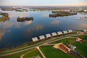 Nederland, Gelderland, Maasbommel, 15-11-2010. Recreatiegebied De Gouden Ham, onderdeel van rivier de Maas met drijvende woningen aan de Bovendijk. De recreatiewoningen maken onderdeel uit van een complex van buitendijks gebouwde tweede huizen, die (gaan) drijven bij hoog water. De woningen zijn bevestigd aan meerpalen om verschillen in waterhoogte op te vangen. .The Golden Ham recreation site, part of the river Meuse with floating houses on the Bovendijk (Upper Dike). The holiday homes are part of a  complex of houses build outside the dike that will rise and fall with the water level. The houses are attached to bollards to compensate water level fluctuations. .luchtfoto (toeslag), aerial photo (additional fee required).foto/photo Siebe Swart