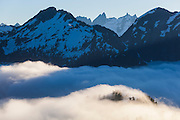 Mountains rise above low clouds, North Cascades National Park, Washington. The Rake, Mount Terror, Mount Degenhardt, and Pyramid Peak - of the remote Picket Range - are visible through a notch below Mount Triumph.