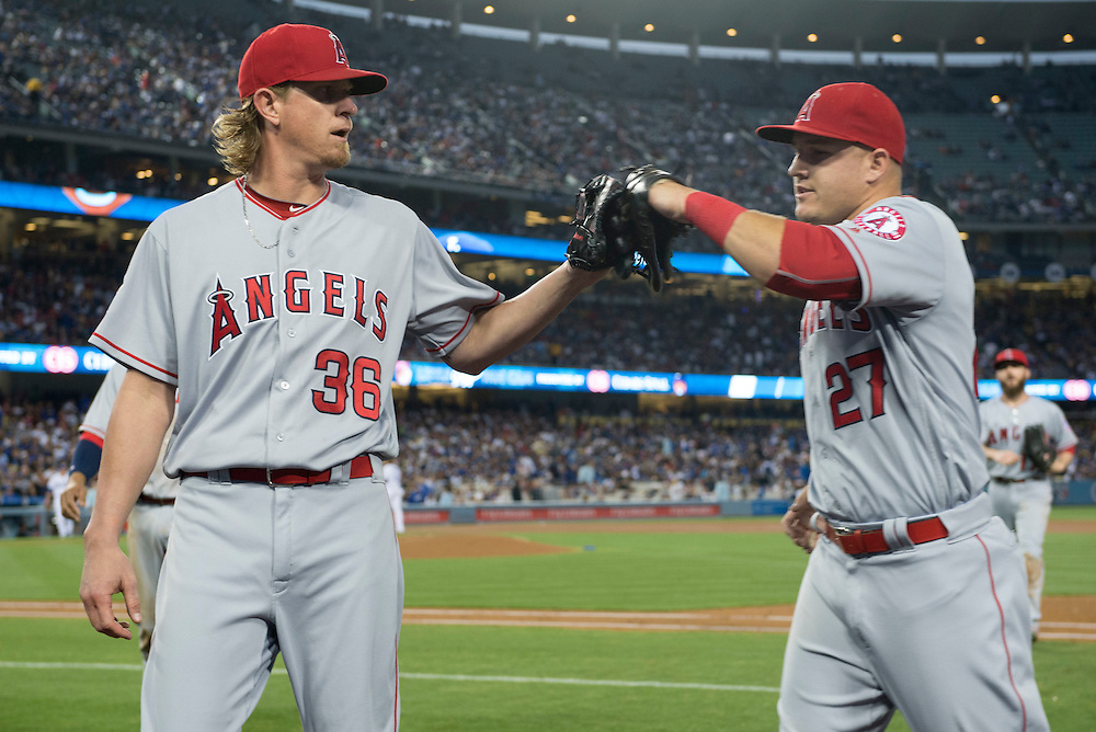 The Angels' Jered Weaver high-fives Mike Trout after his throw got Clayton Kershaw at third during the Angels' 5-1 loss to the Dodgers Tuesday night at Dodger Stadium.<br /> <br /> / //ADDITIONAL INFO:   <br /> <br /> angels.0518.kjs  ---  Photo by KEVIN SULLIVAN / Orange County Register  -- 5/17/16<br /> <br /> The Los Angeles Angels take on the Los Angeles Dodgers in inter-league play at Dodger Stadium Tuesday night.