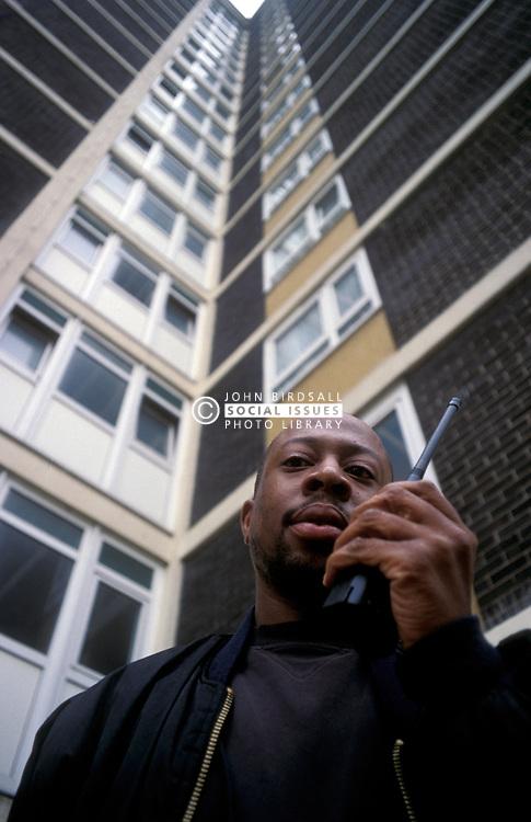 Estate caretaker on radio outside council block Haringey, London UK