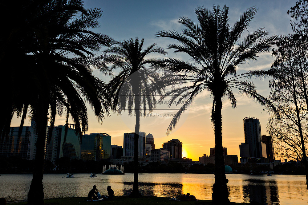 Skyline view over Lake Eola and palm trees at sunset in Orlando, Florida. Lake Eola Park is located in the heart of Downtown Orlando and home to the Walt Disney Amphitheater.