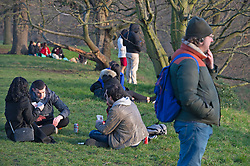 © Licensed to London News Pictures 02/03/2021. Greenwich, UK. A group playing cards as the sun sets. People get out of their homes from a third national Coronavirus lockdown to enjoy the sunset in Greenwich Park, London. Photo credit:Grant Falvey/LNP