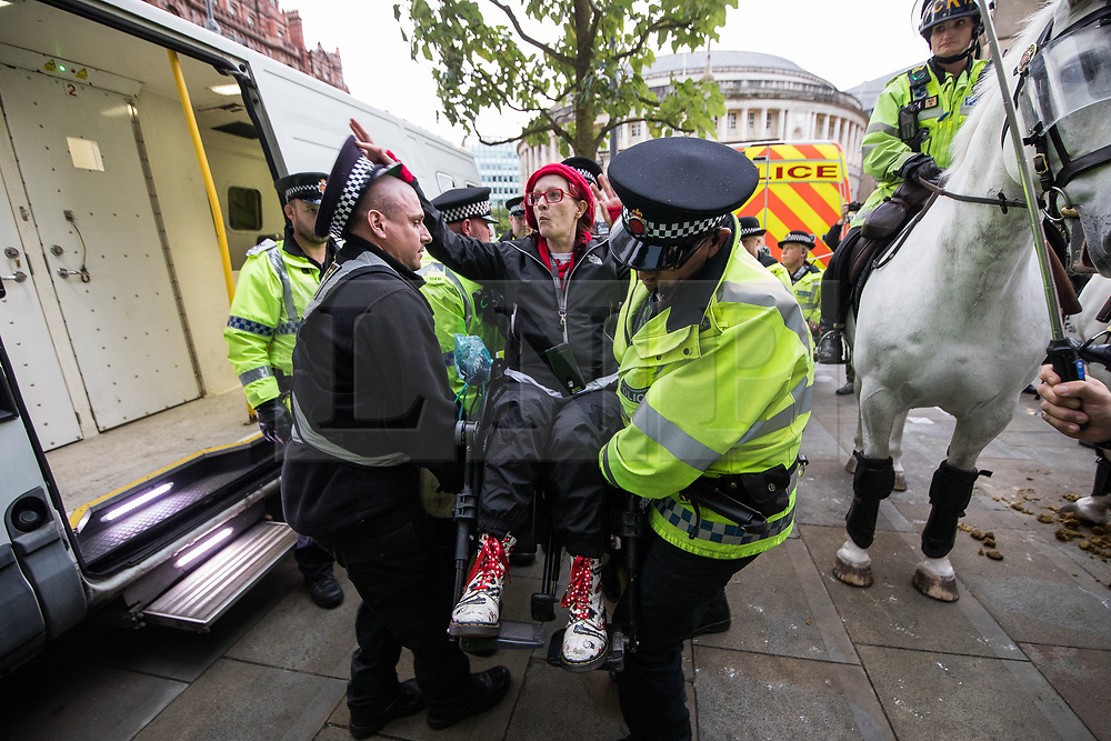 © Licensed to London News Pictures . 01/10/2017. Manchester, UK. Police arrest wheelchair users and lift them in to a police van , amongst anti Tory protesters blocking tramtracks at St Peter's Square opposite the Midland Hotel . People take part in a demonstration against the Conservative Party in Manchester during the Conservative Party Conference , which is taking place at the Manchester Central Convention Centre . Photo credit: Joel Goodman/LNP