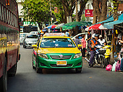 29 NOVEMBER 2015 - BANGKOK, THAILAND:  A taxi in traffic in the Amulet Market on Maharat Road in Bangkok. Hundreds of vendors used to sell amulets and Buddhist religious paraphernalia to people in the Amulet Market, a popular tourist attraction along Maharat Road north of the Grand Palace near Wat Maharat in Bangkok. Bangkok municipal officials announced that they are closing the market and forcing vendors to relocate to an area about one hour outside of Bangkok. The closing of the amulet market is the latest in a series of municipal efforts to close and evict street vendors and markets from areas that have potential for redevelopment. The street vendors were evicted from the area on Sunday, Nov. 29.      PHOTO BY JACK KURTZ
