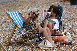 © Licensed to London News Pictures. 14/06/2014. Brighton, UK. Two woman enjoying their time on Brighton beach. Cloudy and the occasional shower hasn't stopped people from visiting Brighton and spending the day at the beach. Photo credit : Hugo Michiels/LNP