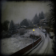 Snow in the countryside on a small road with houses and cars