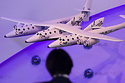 Audience silhouette and scale model of Virgin Galactic's WhiteKnightTwo space vehicle with SpaceShipTwo in the middle at air show PR event. Designed by Robert Morgan & James Tighe, the Scaled Composites Model 348 White Knight Two (WK2) is a jet-powered cargo aircraft which will be used to launch the SpaceShipTwo spacecraft. It is being developed by Scaled Composites as the first stage of Tier 1b, a two-stage to suborbital-space manned launch system. WK2 is based on the successful mothership to SpaceShipOne, White Knight, which itself is based on Proteus.