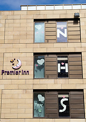 Edinburgh, Scotland, UK. 18 April 2020. Views of empty streets and members of the public outside on another Saturday during the coronavirus lockdown in Edinburgh. Message of support to NHS in windows of Premier Inn hotel. Iain Masterton/Alamy Live News