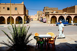 A man in traditional dress strolls passed a pavement cafe in a Street  in Tagounite, Morocco<br /> <br /> (c) Andrew Wilson | Edinburgh Elite media