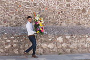 A Mexican man carries a flower arrangement to be used in creating an altar celebrating El Viernes de Dolores during Holy Week March 23, 2018 in San Miguel de Allende, Mexico. The event honors the sorrow of the Virgin Mary for the death of her son and is an annual tradition in central Mexico.