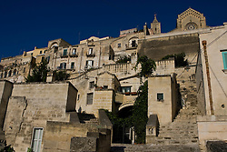 Matera, Basilicata, Italy - The Sasso Barisano, one of two ravines honeycombed with cave dwellings that make up Matera, with the tower of the Duomo at top. The town in a UNESCO World Heritage Site.