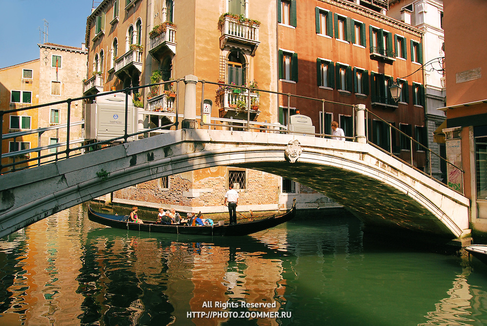 Long bridge over canal in Venice. Tourists in gondola under the bridge.