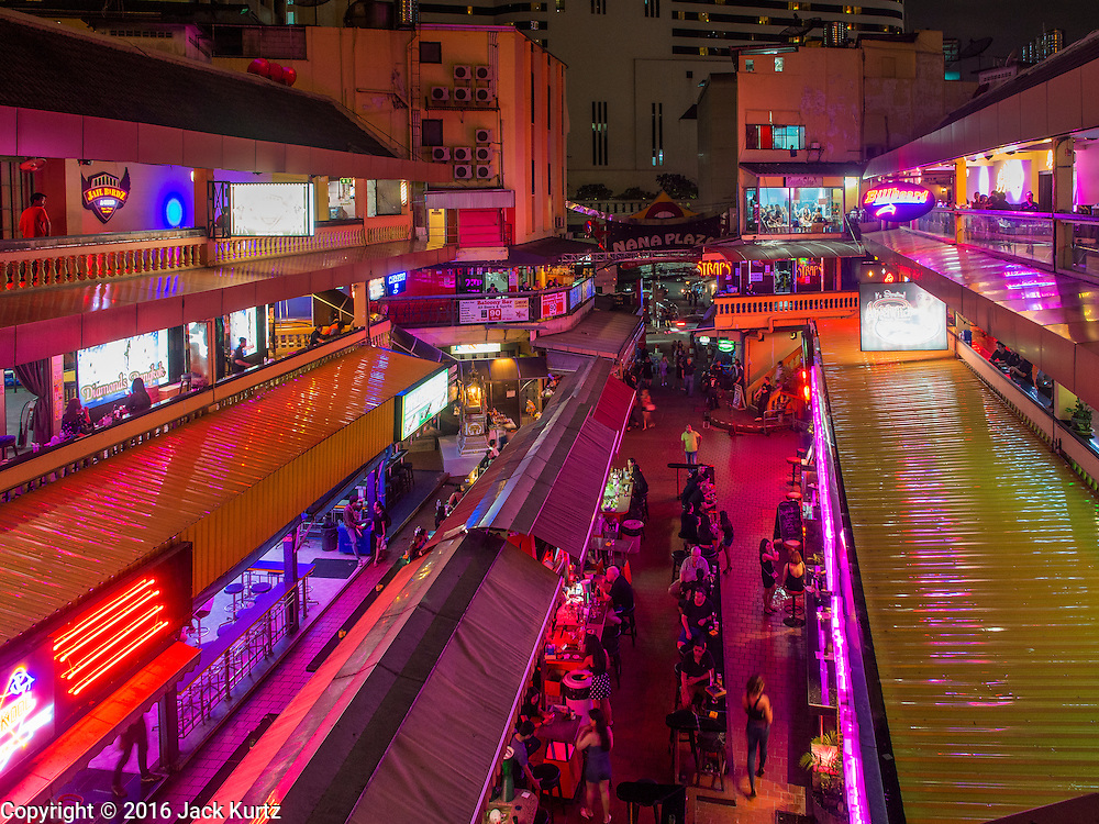 """03 NOVEMBER 2016 - BANGKOK, THAILAND:  Lights are dimmed at Nana Plaza, one of Bangkok's most famous """"adult entertainment districts."""" Bangkok's infamous nightlife has been scaled back during the mourning period for the late Bhumibol Adulyadej, King of Thailand. The revered King died on 13 October 2016 at age 88. The government declared a year of mourning. The government ordered Thailand's notorious adult entertainment districts to turn off their neon lights, dress employees in black and ensure that music can't be heard on the street in front of the venues for 30 days, the government said the entertainment venues could resume normal operations on 14 November.       PHOTO BY JACK KURTZ"""