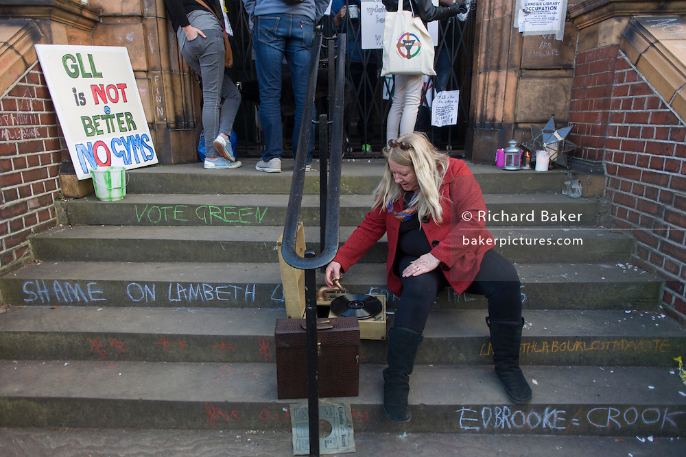 A DJ plays discs on a wind-up gramophone outside Carnegie Library in Herne Hill, south London while occupiers remain inside the premises on day 6 of its occupation, 5th April 2016. The angry local community in the south London borough have occupied their important resource for learning and social hub for the weekend. After a long campaign by locals, Lambeth have gone ahead and closed the library's doors for the last time because they say, cuts to their budget mean millions must be saved.