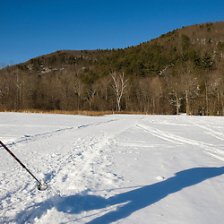 A man snowshoes in a field near the Ashuelot River in Surry, New Hampshire.  Army Corps of Engineers Recreation Area.