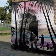 """Nederland Den Haag 31 augustus 2008 2080831 Foto: David Rozing..Muurschildering in achterstandswijk Schilderswijk. In de wijk zijn verschillende muurschilderingen aangebracht om het multiculturele karakter van de schilderswijk weer te geven. Per muur is een beeld gecreerd uit een cultuur: Indiaas, Afrikaans, Nederlands, Surinaams, Antilliaans en Arabisch.  Doel van de muurschildering: """" Om graffiteurs en onroerend goed eigenaren op een kunstzinnige wijze met elkaar te laten samenwerken en onder afspraak dat de graffiteur ophoudt met illigaal taggen. De graffiteur wordt betaald en krijgt de opdracht om deze muurschilderingen aan te brengen. Meer info: Yolande Weerdenburg 06 24613835.De schilderwijk is een van de 40 wijken van Vogelaar. Deze lijst van 40 Nederlandse probleemwijken is op 22 maart 2007 door Minister Ella Vogelaar van Wonen, Wijken en Integratie bekend gemaakt. De minister duidde deze wijken aan met prachtwijken. In deze wijken zullen gedurende de kabinetsperiode Balkenende IV extra investeringen worden gedaan gezien stapeling van sociale, fysieke en economische problemen die zich daar voordoen..De wijk is in de tweede helft van de 19e eeuw gebouwd. Het is een van de armste wijken in Nederland. Zo'n 87% van de 33.123 geregistreerde bewoners is van niet-Westerse afkomst -- met name Turks, Surinaams en Marokkaans..De Schilderswijk is rijk aan verschillende culturen die boven en naast elkaar leven. Er is veel keuze in voedselaanbod in cafés, kleine restaurants, bars en supermarkten. Er is de Haagsche markt en er zijn winkels waarin verschillende culturen hun deur openen om iets nieuws te verkopen, zoals sieraden- en kledingwinkels. Allerlei stedelijke activiteiten liggen op loopafstand van de Schilderswijk. De Haagse binnenstad ligt 5 minuten lopen vanaf de rand van de Schilderswijk. Tram en ander openbaar vervoer zijn te bereiken op 5 tot 10 minuten loopafstand...Foto David Rozing"""