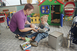 Young boy with Cerebral Palsy playing with playgroup worker on Children's ward in hospital,