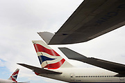 "Wing tips and tails from British Airways 747-400 jet airliners are almost touching during their respective turnrounds while on the apron outside Heathrow Airport's Terminal 5 building. A passing aircraft taxies past on the left and the other two planes have wingtip devices increase the lift generated at the wingtip which smooth the airflow across the upper wing near the tip and reduce the lift-induced drag caused by wingtip vortices. This improves lift-to-drag ratio and increases fuel efficiency, in powered aircraft. From writer Alain de Botton's book project ""A Week at the Airport: A Heathrow Diary"" (2009)."