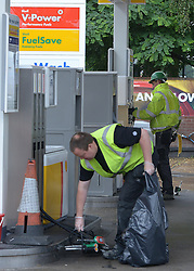 © Licensed to London News Pictures. 16/07/2012. London, UK A workman removes locks. Shell pumps have been closed by protesters and locked together with bicycle locks. A shell petrol station on Uxbridge Road, West London today. Greenpeace campaigners have successfully shut down shell stations across London by removing the fuses from the emergency fuel cut off switch. Photo credit : Stephen Simpson/LNP