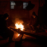 Migrants keep warm near a open fire in one of the abandoned warehouses in central Belgrade. The constant open fires, mainly fuelled by old railway sleepers scattered around the area, fill the warehouses with a tick and intense smoke.