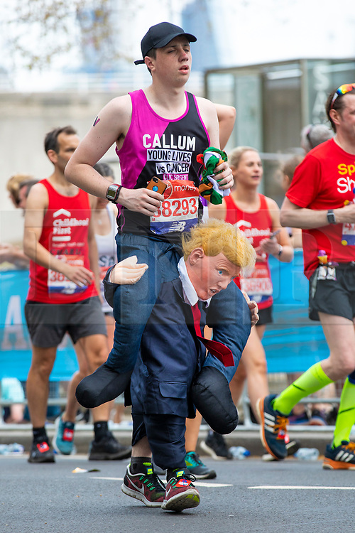 © Licensed to London News Pictures. 22/04/2018. London, UK. A fancy dress marathon runner appears to be carried along Embankment on Donald Trump's shoulders during the Virgin Money London Marathon 2018. Photo credit: Rob Pinney/LNP