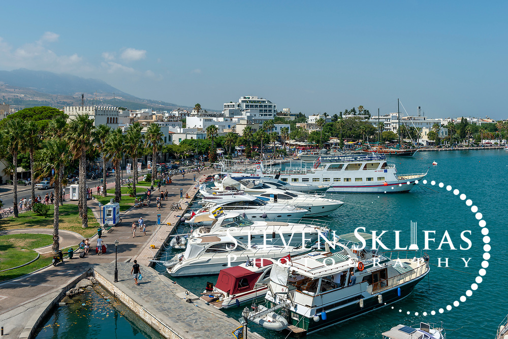 Waterfront view and boats docked in the harbour of Kos town, the capital of the Greek island of Kos. Kos is part of the Dodecanese island group and birthplace of the ancient physician and father of medicine, Hippocrates.